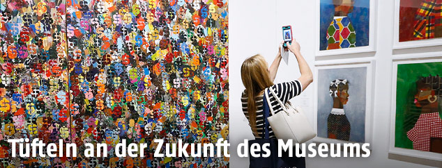 Eine Frau mit Smartphone vor Bildern