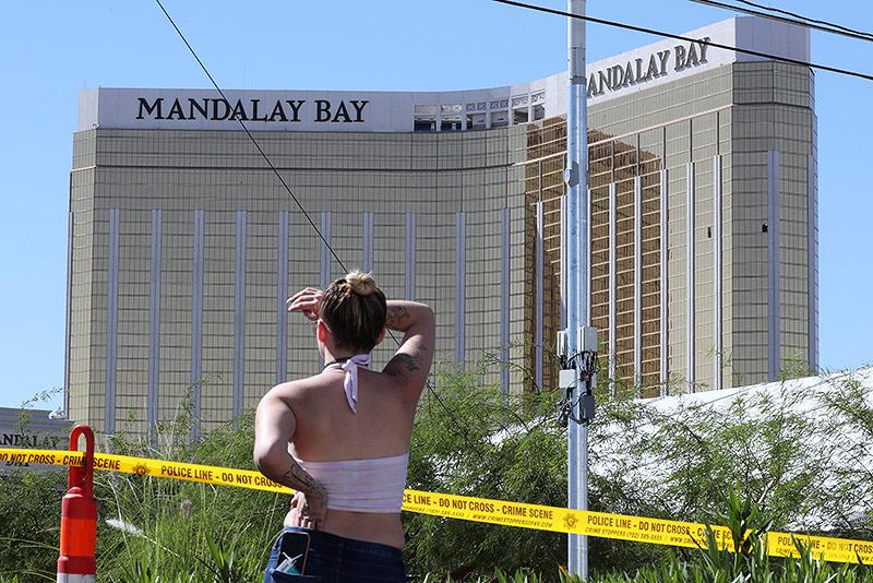 Frau betrachtet vor einer Polizeiabsperrung das Mandalay Hay Hotel in Las Vegas