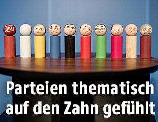 Holzfiguren mit Gesichtern der Spitzenkandiaten in den Parteifarben