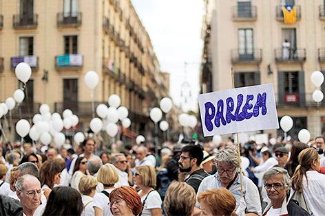 Menschen in weißer Kleidung und Luftballons in Barcelona