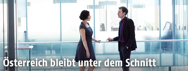 Mann und Frau sprechen in einem Bürohaus miteinander
