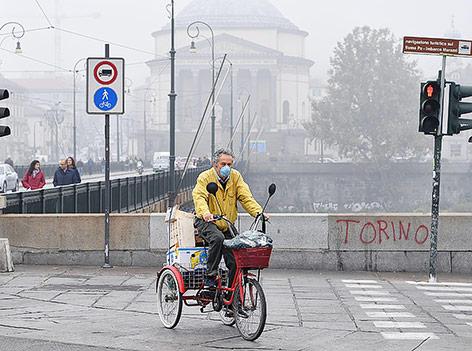 Radfahrer mit Schutzmaske im von Smog betroffenen Turin