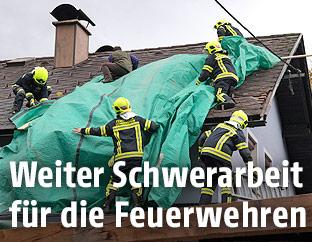 Feuerwehrleute versuchen ein Dach mit einer Plane abzudecken