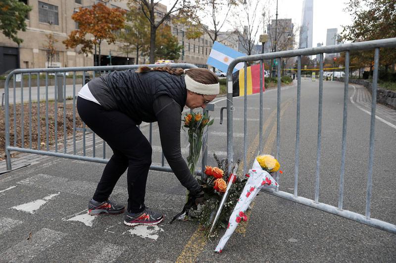 Frau hinterlegt Blumen am Anschlagsort in New York