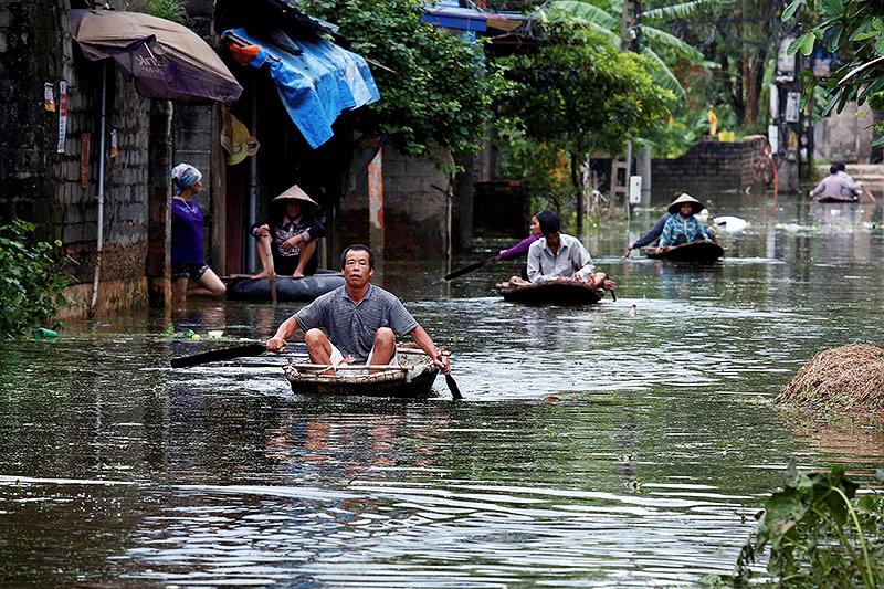 Menschen in Booten in einem überfluteten Dorf