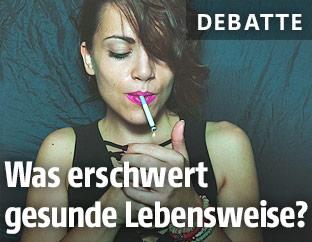 Eine Frau zündet sich eine Zigarette an