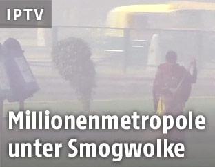 Frau geht durch das durch Smog betroffene Neu Delhi