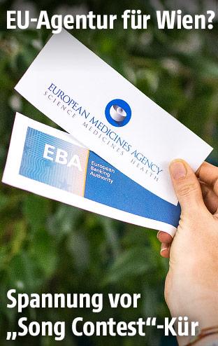 Frau hält die Logos der EU-Agenturen EMA und EBA in die Kamera