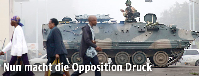 Menschen in Harare gehen an einem Panzer vorbei