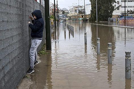 Mann in Athen versucht angelehnt an einer Mauer über eine überflutete Straße zu kommen