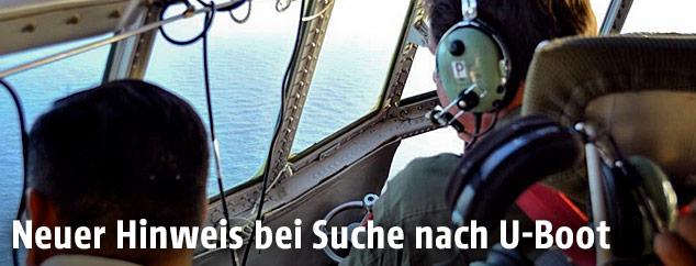 Suchkräfte blicken vom Flugzeuge aius aiuf das Meer
