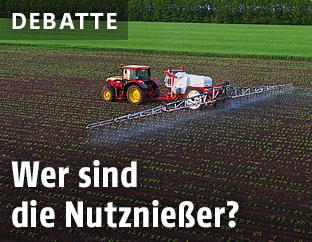 Ein Traktor auf einem Feld sprüht Pestizide