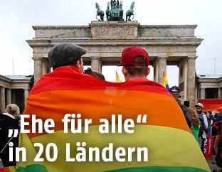 Pärchen in Regenbogenfahne eingewickelt vor dem Brandenburger Tor in Berlin