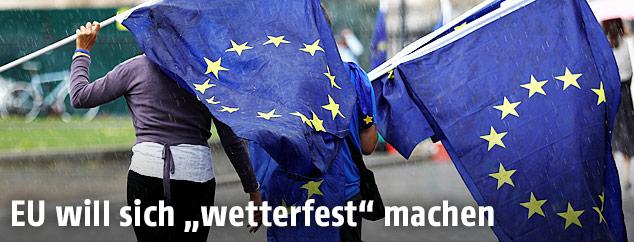 Eine Frau hält eine EU-Flagge über ihren Kopf