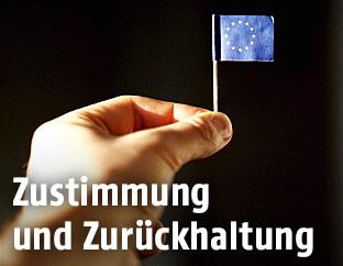 Eine Hand hält eine kleine EU-Flagge aus Papier