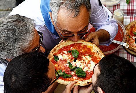 Pizzabäcker aus Neapel riechen an einer Pizza Margherita