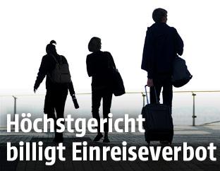 Silhouetten von drei Reisenden auf einem Flughafen