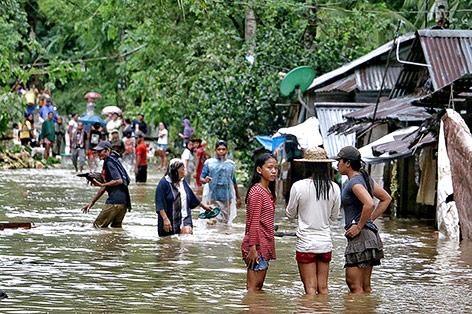Menschen stehen auf einer überfluteten Straße