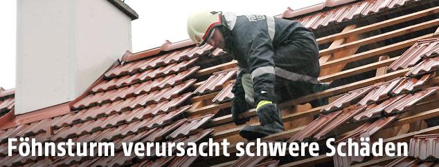 Feuerwehrmann fixiert ein Dach an einem Wohnhaus