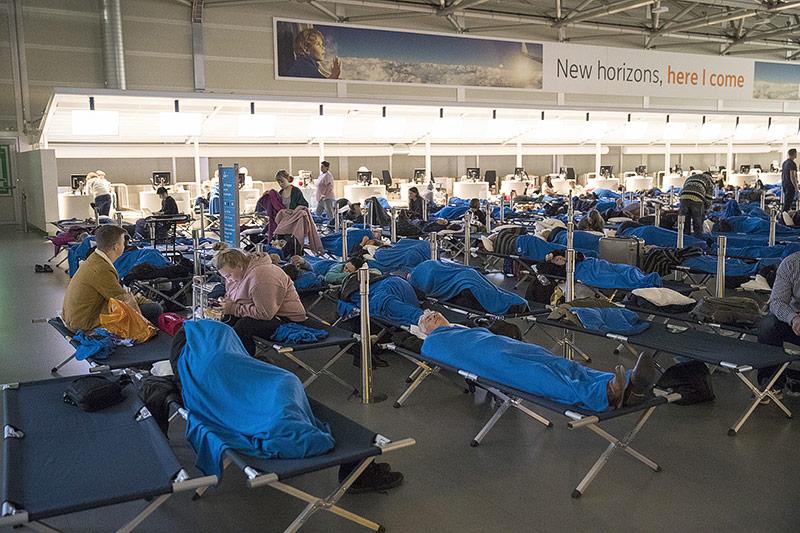 Passagiere schlafen auf Feldbetten auf dem Flughafen Schiphol in Amsterdam