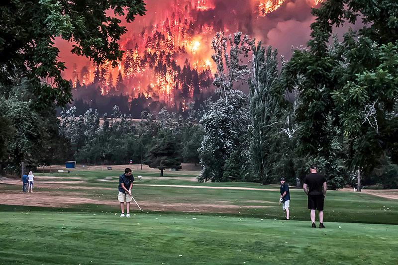 Mehrere Menschen spielen Golf, während im Hintergrund ein Waldbrand tobt