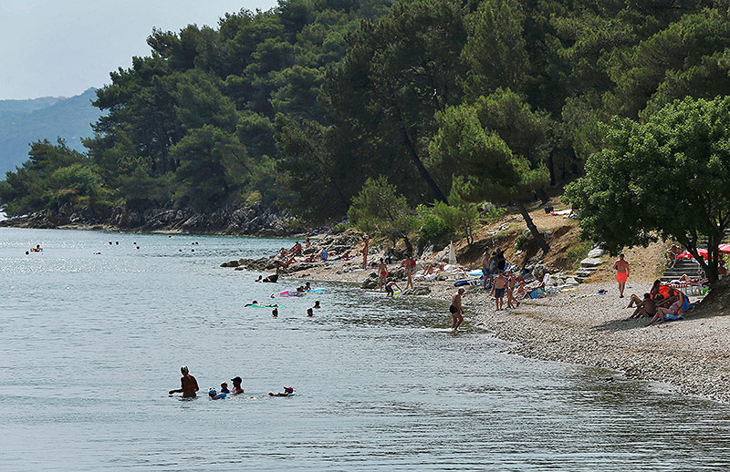 Menschen baden in der Bucht von Piran