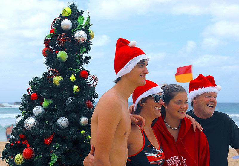 Familie posiert mit Weihnachtsmützen am Bondi-Beach in Sidney