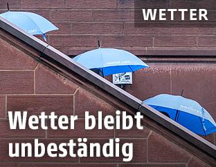 Personen mit Schirmen gehen Stufen hinunter