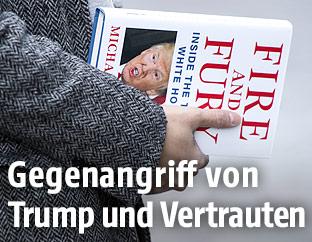 """Frau hält ein Exemplar des Buchs """"Fire and Fury: Inside the Trump White House"""""""