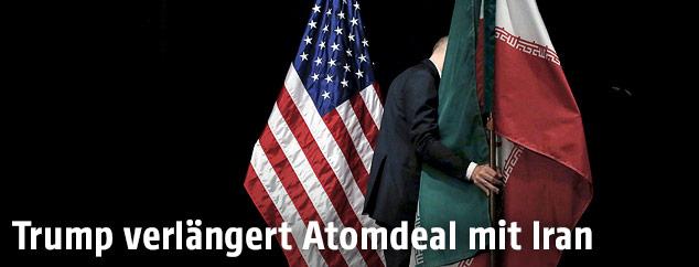 Mann trägt Irans Flagge und US-Flagge weg