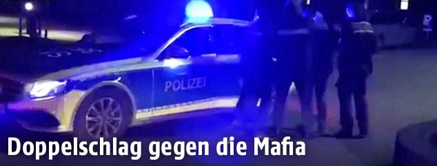 Deutsche Polizisten führen einen Verdächtigen ab