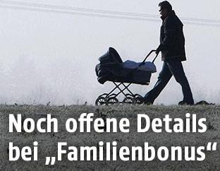 Vater mit Kinderwagen spaziert im Nebel