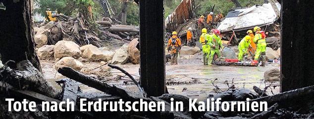 Rettungskräfte vor zerstörten Häusern