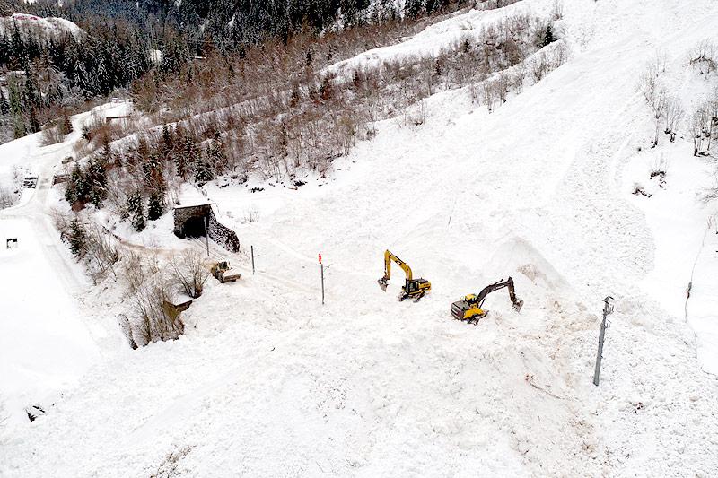 Bagger auf der schneebedeckten Zugstrecke