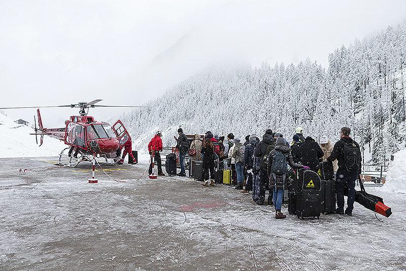 Touristen warten auf dem Heliport der Air Zermatt für einen Flug per Luftbruecke ins Tal nach Raron