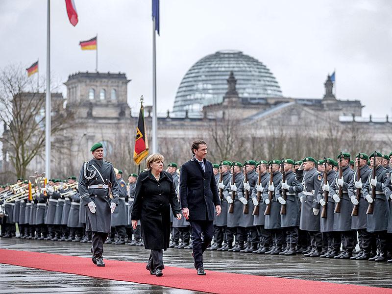 Die deutsche Bundeskanzlerin Angela Merkel begrüßt Österreichs Bundeskanzler Sebastian Kurz vor Bundeswehrsoldaten
