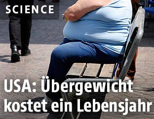 Ein übergewichtiger Mann sitzt auf einer Bank
