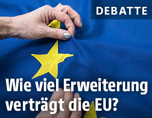 Hände an einer EU-Flagge