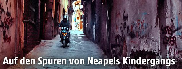 Mopedfahrer in einer engen Straße in Neapel
