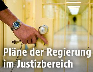Ein Justizbeamter öffnet im Gefängnis eine Gittertür
