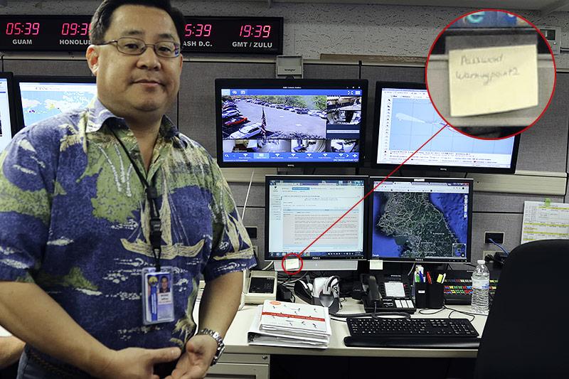 Offizier Jeffrey Wong vor zwei Bildschirmen mit Post-it-Zettel, auf dem das Passwort zu lesen ist