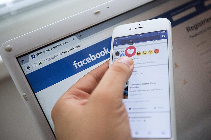 Person verwendet auf dem Handy die Facebook-APP