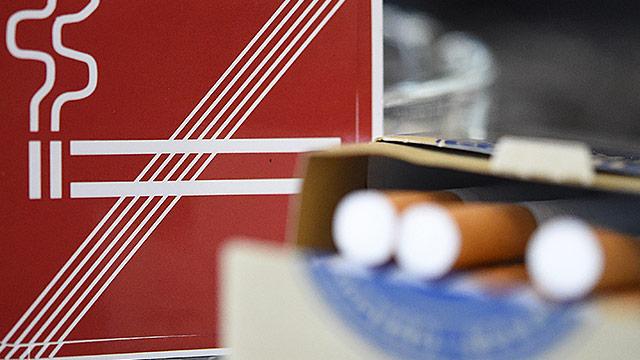 Zigaretten vor einem Rauchverbotschild