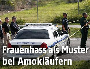 Polizisten stehen bei einem Polizeiauto
