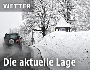 Auto fährt in Winterlandschaft auf Straße