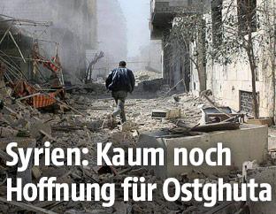 Mann läuft durch eine völlig zerstörte Straße in Ostghuta