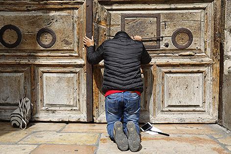 Gläubiger Mensch kniet vor dem versclossenen Eingang der Grabeskirche