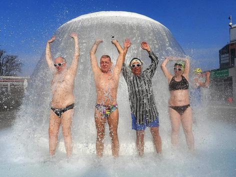 Besucher im Sonnenbad in Karlsruhe unter einer Wasserdusche im Freien