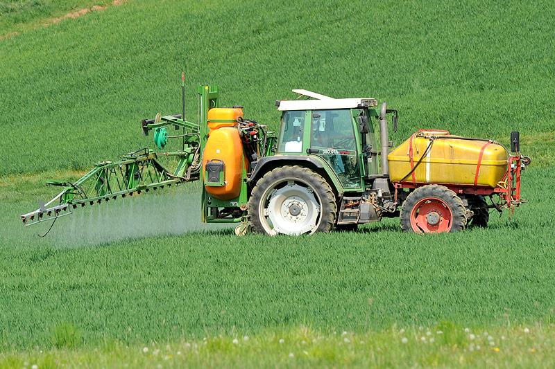 Ein Traktor versprüht Pflanzenschutzmittel auf einem Feld