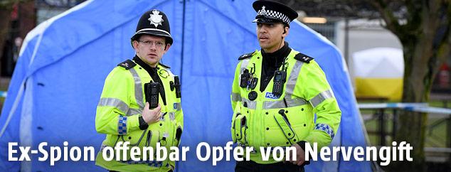 Polizisten vor einem Zelt